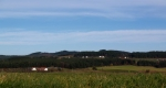Pod hřebeny  jsou všude rozesety malebné domky, svítící svou bělobou daleko do kraje, jako zde pod Haberským vrchem.