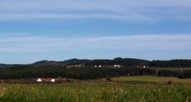 Pod hřebeny hor jsou všude rozesety malebné domky svítící svou bělobou daleko do kraje, jako například zde, pod Haberským vrchem.