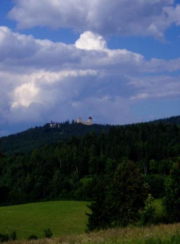Pohled ke hradu od Kašperských hor. V okolí jsou nově vyznačeny turistické naučné stezky.