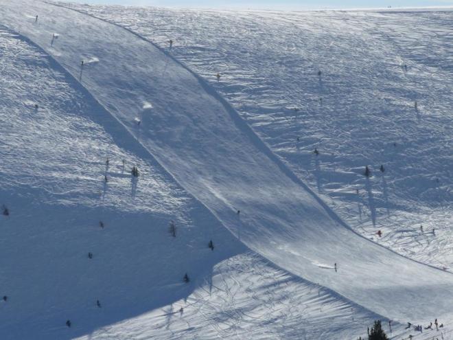 Nízké zimní slunce osvětlovalo sníh zvedaný lyžaři na chvilku do vzduchu, jen aby se blýskl svou krásou.
