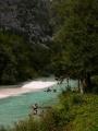 Rybář, kajakáři a v řece se brouzdající turisté, kemp Klin