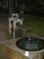 Voda stékající do skleněných rukou u zbořené kaple.