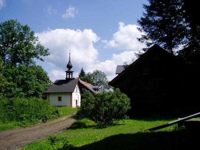 Kolem kaple mírně stoupáme k vrchu Kozinec a míříme k Flusárně. Okolní krajina opravdu připomíná kozí hřbety a její zvlnění je velmi zajímavé.