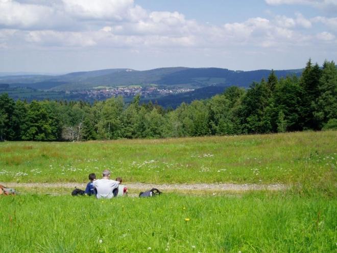 Na Flusárně je nádherný rozhled a tak se kocháme výhledy na Kašperk a Kašperské Hory. Po krátké přestávce jdeme dél. Terén se začíná tvrdě zvedat a my máme před sebou Zhůří a hohutnou Huťskou horu (1 187m).