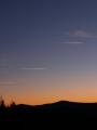 Nebe se zbarvilo doruda a jen bílé čárky putujících letadel ruší mýtický okamžik hodiny mezi psem a vlkem. Velký Plešný se spolu s Chlumem topí v krvi, aby zanedlouho zmizely v noci plné přízraků.