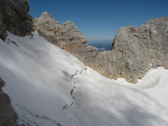 Na snímku je vidět cestička po docela strmé části ledovce (cepín se hodil, i když jsem neuklouzl). Trhlinu lze naštěstí přejít po jednom sněhovém můstku (jsem rád, že jdu poslední). Myslím, že jsem na fotce vlevo nahoře. (Martina)