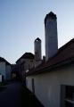 Vysoko ční komíny nízkých domků v okolí kláštera.