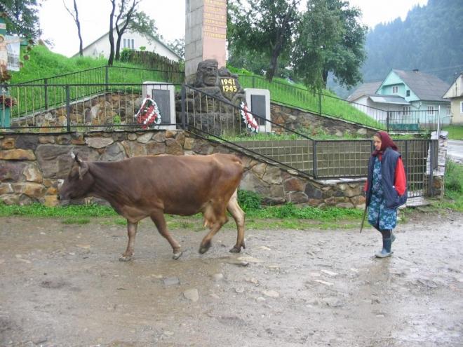 Babička s krávou před památníkem
