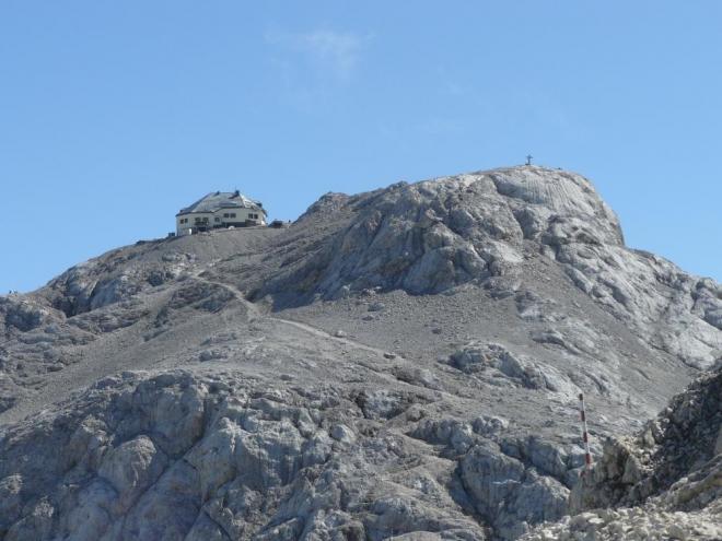 Chata, předvrchol a za ním vrcholový kříž.