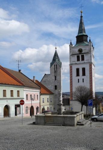 Pohled na kostel i zvonici. Farní kostel Navštívení Panny Marie v dolní část náměstí je připomínán poprvé v roce 1365, kdy zřejmě vznikly presbytář, sakristie a jižní portál lodi.