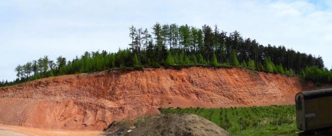 Lom Červená vrch. Jeho čevená barva nás provází na lesních cestách, tedy těch, které unikly vyasfaltování.