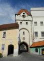 Na západní straně je brána ozdobena kamenným reliéfem městského znaku v renesanční kartuši.