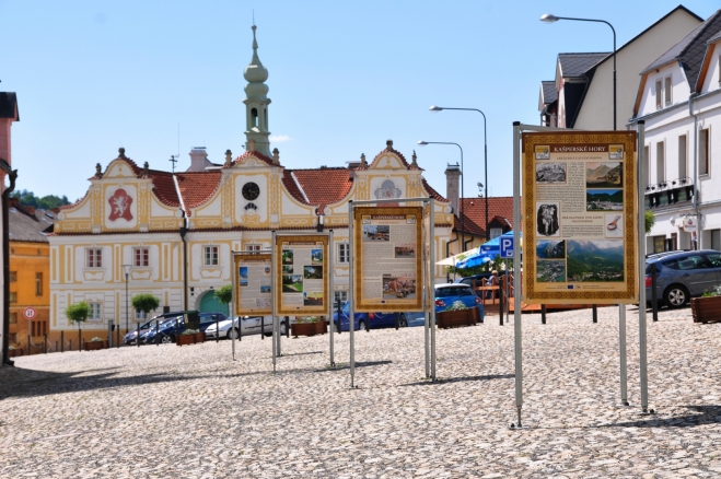 Informační cedule jsou vkusně rozmístěny mezi cestou a kostelem na náměstí.