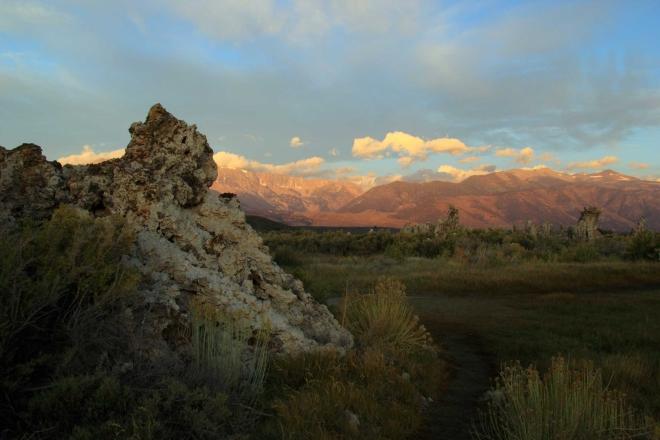 Vycházející slunce začíná osvětlovat okolní hory, jezero je ještě ve tmě