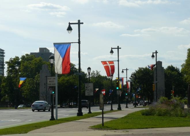 Vlajky podél ulice směřující od radnice k muzeu umění. Ulice je obklopena parky a muzei, což působí hezky.