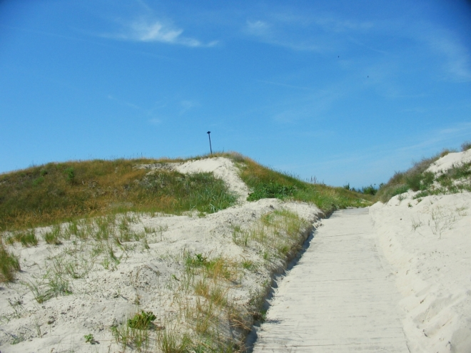 Přes písečný val k moři se smí přecházet pouze po připravených cestách. Tento chodník vypadá zpočátku slibně, ale pro fotku pobřeží najdeme radši místo, kde nejsou jen samí nazí chlapi.