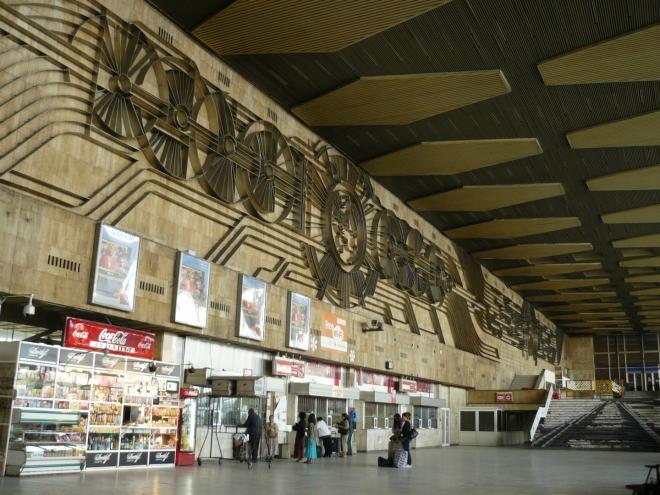 Vlakové nádraží, kde čekáme na Lídu, je ukázkou socialistické monstrózní stavby. Koleje na schodech vpravo se mi ale líbí.