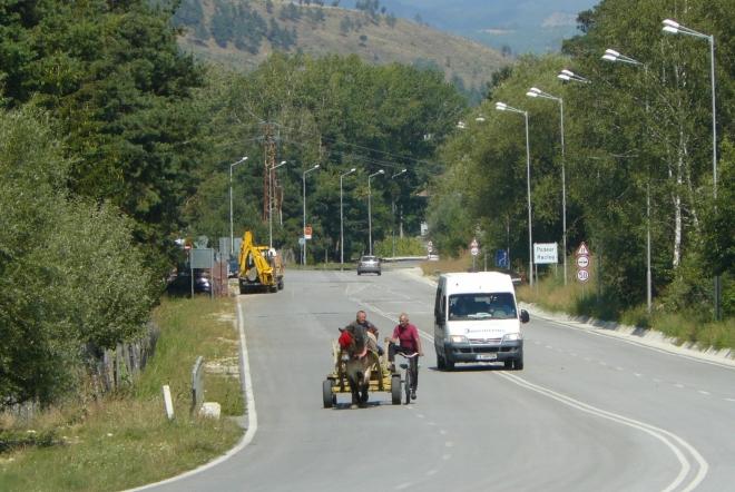 Povoz na silnici jede v klidu, i když by tam dle značek být neměl. Vozka dokonce cestou s někým klábosí. Za moment jsme si ho stopli, má vzadu víc než dost místa na nás i naše bágly. Svezl nás přes nudný kus silnice až ke křižovatce, kde jsme se odpojili na silnici k horám.