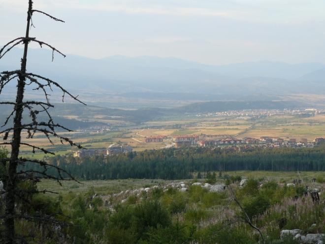 Pohled na Razlog z tábořiště. V popředí přímo pod patou hor je pás louky, možná následek nějaké smrště. Vzadu se letmo rýsuje Rila.
