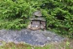 Dokonce objevujeme i vrcholovou knihu ukrytou v kamenné ohrádce.