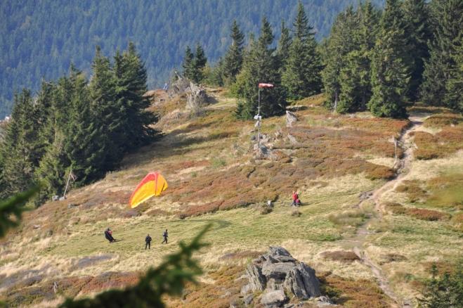 Již z výstupu na vrcholek se otevírá krásný pohled na horskou louku, kde mají základnu vyznavači paraglidingu. Vzdušné proudy zde pro ně vytváří ideální podmínky a tak jejich padákové kluzáky, jak zní správný název křídla, nepřetržitě krouží nedaleko od nás.