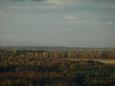 severně v oparu se zoomem komín mělnické elektrárny a České středohoří s Řípem