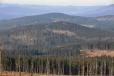 Nejblíže je vidět Dlouhý hřbet, za ním Křemenná s dvěma vysílači a vzadu čouhá hřeben hraničních hor, kde můžeme spíš tušit Luzný, Mokrůvku i Roklan.