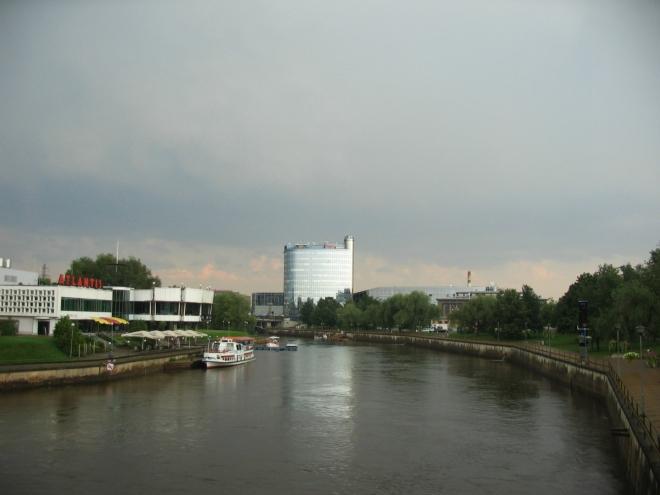 Přecházíme řeku Emajõgi, v pozadí druhá nejvyšší budova ve městě. Na místě mostu, z něhož fotím, stával do druhé světové války starý kamenný most krásně navazující na náměstí, dnes jej však připomíná pouze drobná maketa. I z různých starých snímků je vidět, jak moc se tehdy město v krátké době proměnilo. Škody zde působily obě bojující strany, zrovna tento most mají na svědomí Němci.