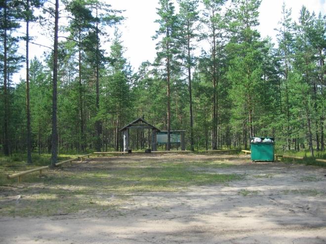 Vybavení je na naše potřeby až luxusní, v lese je roztroušeno pár dřevěných přístřešků, stůl, lavičky, ohniště, záchod, sekera, dřevo k topení a další vymoženosti. Tento plácek pro stany však asi nevyužijeme, je plný střepů.