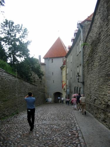 """Toompeu po kratším odpočinku opouštíme nejstarší ulicí v celém Tallinnu. Pikk Jalg (""""Dlouhá noha"""") bývala po mnoho staletí jedinou řádnou spojnicí horního a dolního města. Brána nám teď poslouží jako úkryt před deštěm."""