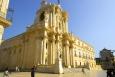 Řecký chrám bohyně Athény (dnes Dóm, městská katedrála) byl postaven po vítězství nad Kartágem v roce 480 př. n. l. na návrší ostrova Ortigie. Byla na něm socha bohyně s pozlaceným štítem, který sloužil přes den mořeplavcům. V 7. století našeho letopočtu byl přeměněn na baziliku. Zemětřesení v letech 1542 a 1693 zbouralo některé části chrámu. V letech 1728–57 bylo postaveno barokní západní průčelí od Andrei Palmy z Palerma, za nímž se ukrývá původní zachovalý Athénin chrám.