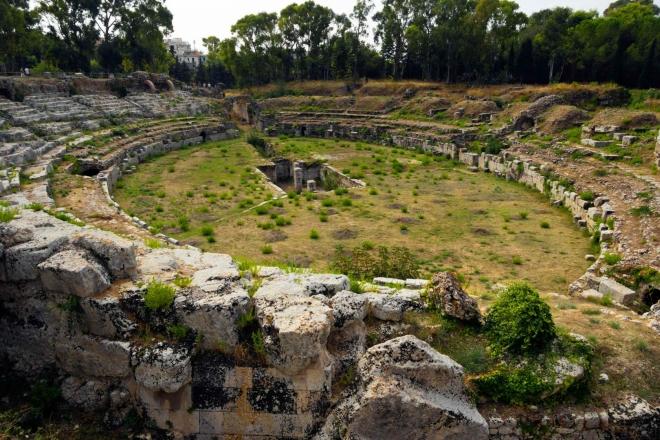 Římský amfiteátr byl postaven kvůli gladiátorským představením a pochází ze 3. až 4. stol. před Kristem. Byl vytesán do skály. Ač se to nezdá, byl obrovský a velikostí ho překoná jenom amfiteátr ve Veroně a samozřejmě Colosseum (!). Bohužel za nadvlády Španělů sloužil amfiteátr jako zdroj kamene pro opevnění, takže z něho moc nezbylo.
