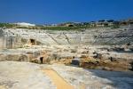 Řecké divadlo. Se stavbou se začalo v 5. stol. př. n. l., ale kompletně bylo divadlo dostavěno v letech 238 – 215 př. n. l. za vlády Hierona tak, že sedadla byla vysekána do skály. Kapacita hlediště byla 16 000 diváků a v průběhu let bylo divadlo mnohokrát upravováno a přestavováno. Za římské vlády bylo divadlo uzpůsobeno i námořním hrám (Naumachie). Původně mělo 61 řad (nyní zbylo 46), rozdělených do 9 sektorů vnitřními schodišti. Šířka hlediště je 138 m a orchestra měla 16 m. Některá sedadla nesou jména předních Syracusanů, např. členů rodiny Hierona II. Nad hledištěm je několik umělých jeskyní, včetně Nymphanea.