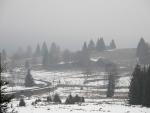 Nad Stožcem se válí mlhy. Svah, po kterém vede lyžařská stopa, je zcela holý.