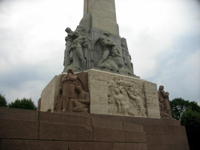 Dolní část pomníku zdobí ze všech stran sousoší a reliéfy, které zobrazují události z lotyšské historie a symbolicky i některé prvky lotyšské kultury.