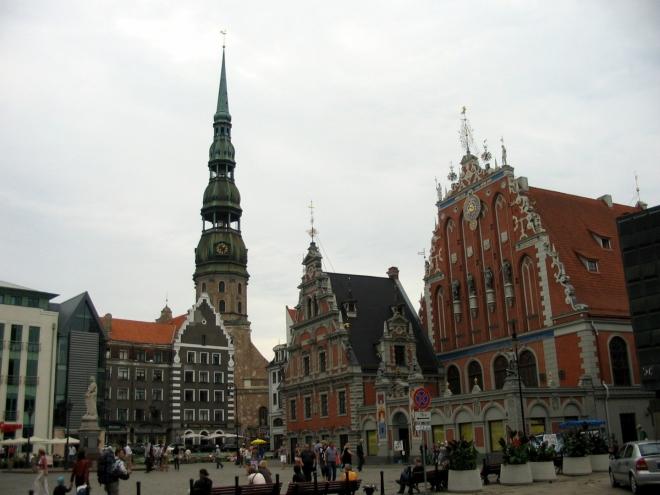 Tohle už je typický obrázek z Rigy, Radniční náměstí s bohatě zdobenými domy a vyčnívajícím kostelem svatého Petra. Šedý dům před kostelem byl přistavěn za dob SSSR, v případě budovy stojící zcela vlevo si nejsem tak jistý.