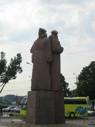Hned za Radničním náměstím, blíže k řece, se nachází náměstí Lotyšských střelců (Latviešu strēlnieku laukums) s tímto pomníkem. Lotyšští střelci byli jednotkou ruské armády, která za první světové války pomáhala bránit Pobaltí před německými útoky.