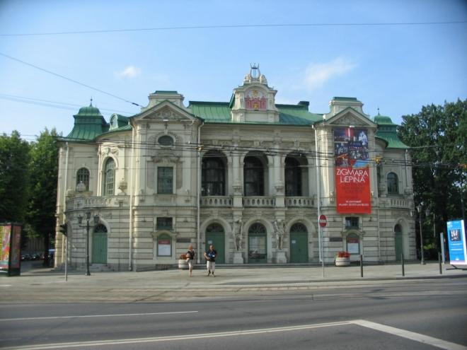 """V této divadelní budově, která byla postavena roku 1902, sídlilo až do jejího uzavření za první světové války """"pouze"""" ruské divadlo. V roce 1918 zde však neproběhlo nic menšího než deklarace nezávislosti Lotyšska a rok později se zde usídlilo nově vzniklé Lotyšské národní divadlo (Latvijas Nacionālais teātris)."""
