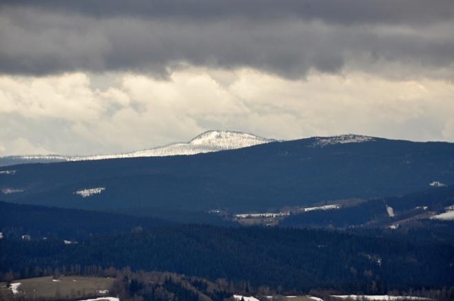 Co přitahuje zrak nejvíc je vzdálený Roklan (1 453m). Se zasněženým vrcholem kontrastuje s černými mraky a zalesněnými nižšími hřbety kolem Medvědí hory (1 223m).