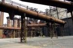 průchod pod konstrukcí potrubí k technickému vchodu Multifunkční auly Gong + pohled na měřič hladiny plynu v někdejším plynojemu, který ředitel Vítkovických železáren viděl z balkónu svého sídla, Vítkovického zámku