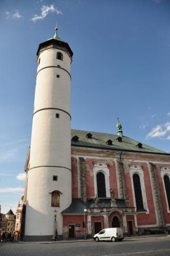 """Kostel Narození Panny Marie s válcovitou věží, která původně ke kostelu nenáležela a bývala hláskou, je dominantou náměstí. První zmínky o kostele se datují k roku 1385, ale pozdější zprávy udávají rok založení 1111. Toto datum je také vepsáno na klenebním oblouku nad kruchtou. Z původní gotické stavby zůstaly zachovány křížové klenby boční lodi a profilované portály. Po požáru města roku 1747 byl kostel v letech 1751-56 barokně přestavěn. Klenutí chrámové lodi je zdobeno freskami F. J. Luxe z roku 1756. Mezi skvosty náleží oltář Narození Panny Marie, dílo pražských mistrů. Ve věži je kromě zvonů Zikmund, Poledník, Hodinka umístěn na ochozu zvonek """"Advent"""" u 15. století, na který se zvoní v předvánočním období."""