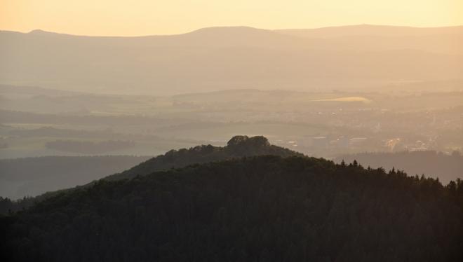 Směrem na západ vystupuje Rýzmberk (665 m n. m.) nad vyšším Škarmanem (689 m n. m.). V pozadí vrcholy Českého lesa, vlevo Škarmanka, uprostřed Starý Herštejn.