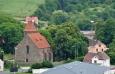 Hřbitovní kostel U Svatých leží při severovýchodním okraji města. Starobylý gotický kostel byl vystavěn v polovině 14. století. Archivní doklad města popisuje, že v roce 1648 úderem blesku a vzniklým požárem byl značně poškozen a ztratil gotickou klenbu lodi. Všechny stavební práce byly dokončeny na tomto kostele až roku 1920. Uvnitř kostela je kamenná renesanční kazatelna a v lodi kostela je umístěno u zdi 15 náhrobních kamenů význačných osobností města. V těchto místech stával do 18. století také kostel sv. Jakuba o němž jsou první zmínky z roku 1037, kdy byl knížetem Břetislavem I. věnován benediktinskému klášteru v Ostrově. Toto darování potvrdil i český král Přemysl Otakar I. r. 1205 a český král Václav IV. r. 1399. Po roce 1406 byly do něho přeloženy všechny bhoslužby. Koncem 18.století kostel sv. Jakuba značně zchátral, byl odsvěcen a prodán r. 1788 domažlickému měšťanu, tkalci Václavu Hájkovi. Vzápětí byl zbourán a dnes po něm není památky. (viz www.domazlice.cz)