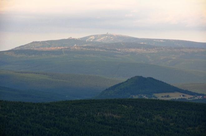 Bukovec více přitažený zoomem. Vysoko nad ním jsou vidět krkonošské Sněžné jámy a Vysoké Kolo (1 509 m n. m.).