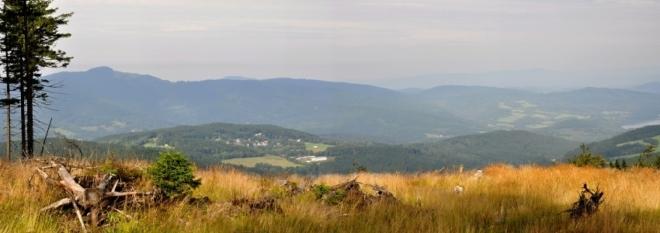 V dáli nad Hojsovou Stráží je vidět vrcholek Ostrého.