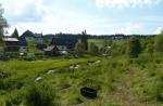 Malebná krajina Kvildy s pastvinou pro ovce v popředí.