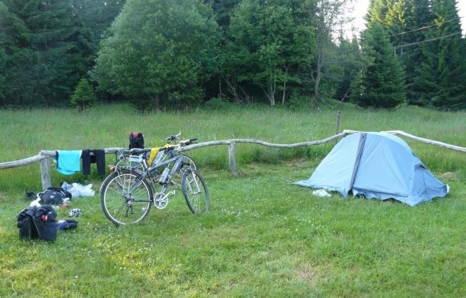 Rozložené věci z brašen, kola a stan