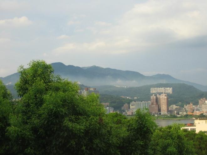 Výhled na druhý břeh řeky Tan-šuej, kde se rozkládá stejnojmenná čtvrť. V pozadí ční tisícovky národního parku Jang-ming-šan (Yangmingshan).