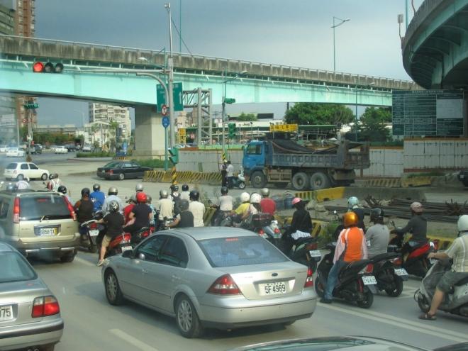 Jak jste si možná už všimli, na Tchaj-wanu jsou velmi populární skútry. Mezi pravým jízdním pruhem a okrajem silnice je stále jakási divoká zóna, kde se předhánějí a kličkují tyto malé stroje, často jedoucí dva nebo tři vedle sebe. Vypadá to docela nebezpečně, ale je to určitě lepší, než kdyby každý z těchto řidičů vyjel do ulic autem. Na některých skútrech se vezou tři lidi najednou, někdy se také místo třetího pasažéra naloží nějaký kus nábytku, třeba židle.