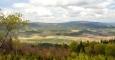 V popředí Mlýnské vrchy Kraví vrch, vlevo vzadu masí Kleti.